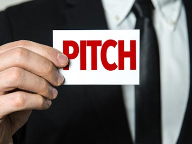 Business man holding card saying 'Pitch'